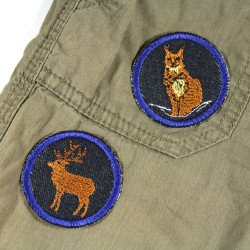 Lynx and deer iron-on patches on trousers. Small round patches suitable for repairing trousers.