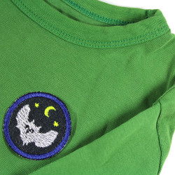 Round iron-on patch with owl as a patch on a green sweater in small size.