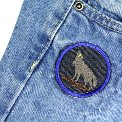 Small patch with wolf ironed on children's pants to repair. Easy quick jeans repair.