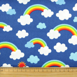 Cotton patchwork fabric by cosmo with clouds and rainbows on blue for quilting