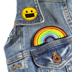 patches smiley and rainbow as iron-on appliques on a denim jacket