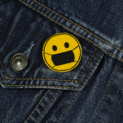 Smiley iron-on patch with face mask as a patch on a denim jacket