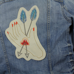 Embroidery on a denim jacket as a large back patch to iron on. Hand with heart and arrow