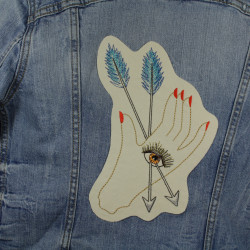 Hand with arrow and eye embroidered as a back patch on a denim jacket