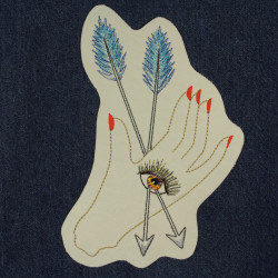 filigree embroidered hand with eye and arrows cream patch on blue jeans