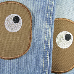 2 brown trouser patches for repairing holes and tears with embroidered eyes