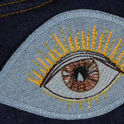 Iron-on eye in brown on light blue jeans for adults